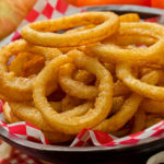 A serving of delicious breaded and deep fried golden brown onion rings.